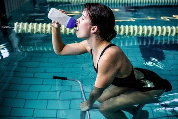 Woman cycling in the pool while drinking water