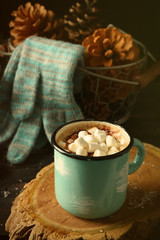 Mug of hot cacao with marshmallow and gloves on black table