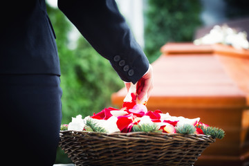 Frau auf Beerdigung streut Rosenblätter auf Sarg