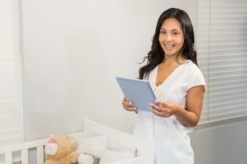 Smiling brunette using tablet