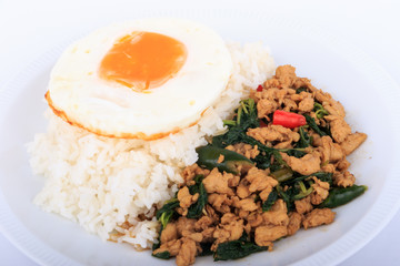 Rice topped with stir-fried chicken, basil and fried egg, fried stir basil with minced chicken on white background (Isolated Background)