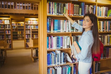 Smiling brunette student picking out book
