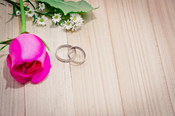 Engage Ring put near Red roses on wood background