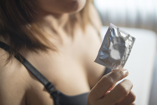 Young woman holding condom package
