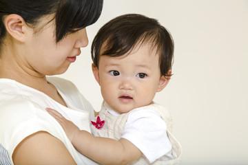 お母さんに抱かれる女の子の赤ちゃん