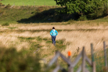 Woman walking on the footpath in the meadow