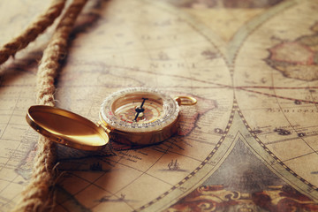 image of old compass and nautical rope on vintage map