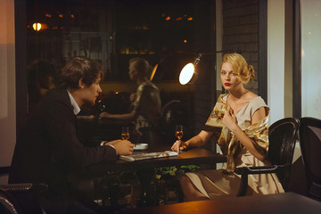 attractive lady in dress and man in suit in cafe.