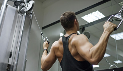 Muscular young man working out on a cable machine