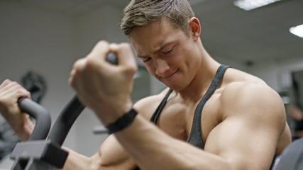 Handsome young man in the gym doing bicep curls on a machine