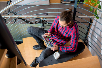 young man sitting on stairs and using tablet PC