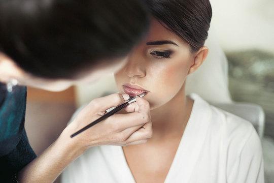 makeup artist makes young beautiful bride bridal makeup