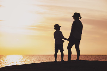 Mother and son silhouettes at the sunset time
