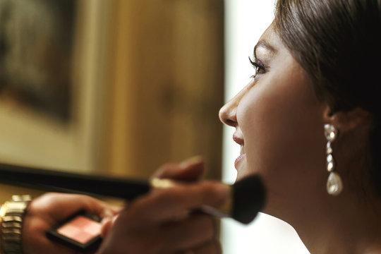 Professional stylist putting on makeup on beautiful brunette bri