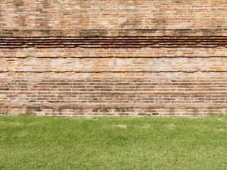 Red brick wall with grass floor