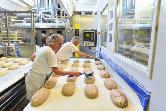 Arbeiter in einer Großbäckerei / Fliessband mit Brotlaibern am Backofen