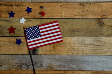 American flag with red, white and blue stars.  Set on pallet wood.