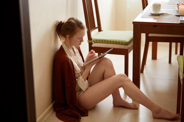 Technology and coziness. Beautiful red haired and freckled young girl with cup of coffee using tablet computer while sitting on floor at home.