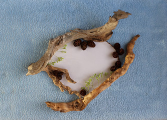 A heart frame of larch cones and dry sticks on a blue and white