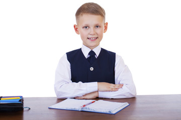 Caucasian school boy at his desk on white background with copy s