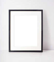 Empty picture frame on white desk