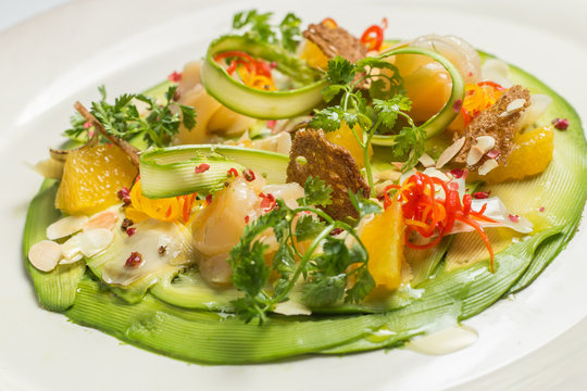Carpaccio of prawns with citrus sauce on a white background. Gourmet cuisine.