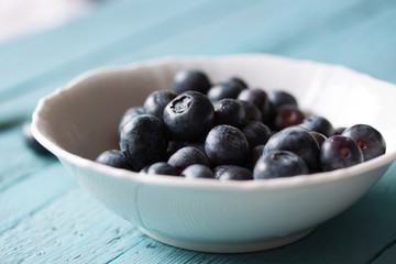 Closeup of fresh ripe blueberries in a bowl on a blue wooden background. Selective focus..