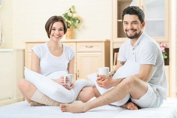 Loving couple drinking tea in bed