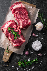 Two raw fresh marbled meat black angus steak ribeye, garlic, salt and  on dark background