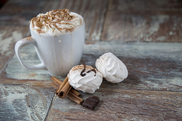 Hot coffee with marshmallows in a cup on the wooden background