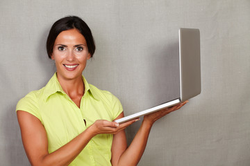 Beautiful brunette lady standing with laptop