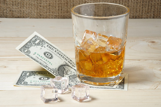 Dollars and glass of whiskey with ice