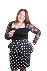 Portrait of sexual buxom girl in dress in black with white polka dots. Big size model