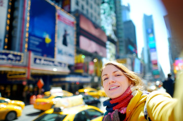 Beautiful young woman taking a selfie on Times Square, New York