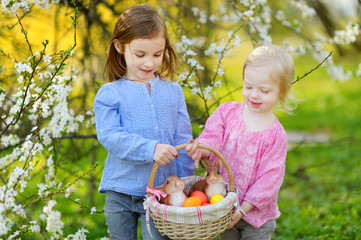 Two little sisters holding a basket of Easter eggs on Easter day