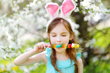 Adorable little girl eating colorful gum candies on Easter