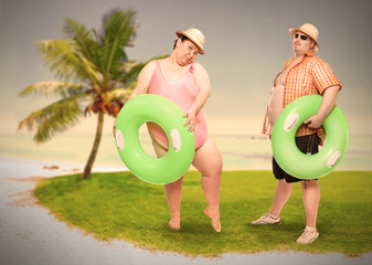 Obese couple in swimsuit with green lifebuoy. Holidays on the beach.Funny people sending greeting from tropical paradise. Warm filtered picture.