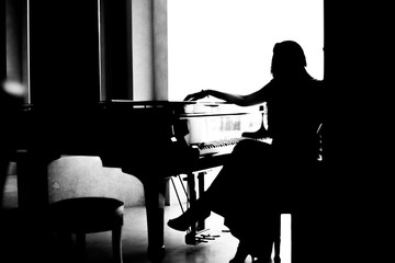 black and white woman silhouette sitting near piano