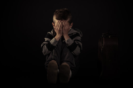 Seated Scared Boy Covering his Face Against Black