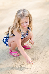 Sweet smiling little girl with long blond hair squatting and drawing in the sand on the beach in summer day
