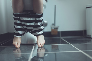 Underwear on Legs of a Boy Using a Toilet at Home