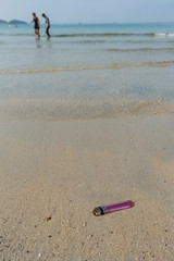 An old and broken lighter polluting the beach