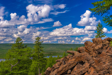 Summer landscape with forest, cliffs and cloudy sky