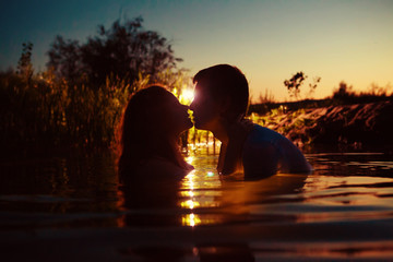 Young couple is kissing in the river on the summer sunset backgr