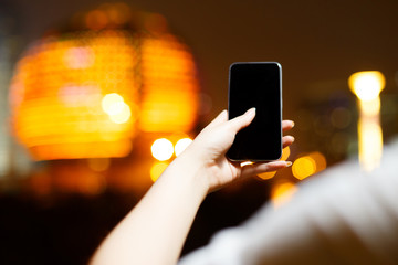 beautiful asian girl using mobile phone at night