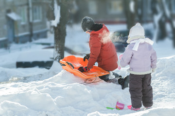 Playing sibling children preparing for winter riding downhill on orange plastic snow slider outdoors