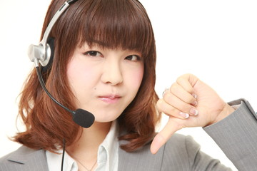 young Japanese businesswoman  of call center with thumbs down gesture