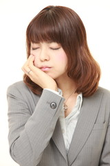 young Japanese businesswoman suffers from toothache