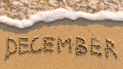 Inscription DECEMBER on a gentle beach sand with the soft wave (months of the year series)