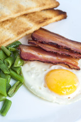Fried egg, bacon, green beans and toasts on light background. English breakfast. Vertical view. Focus on egg and bacon.